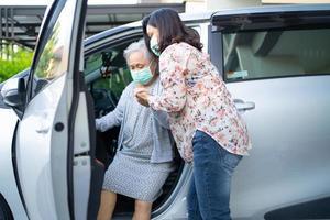 ajudar e apoiar paciente asiático sênior ou idosa senhora sentada na cadeira de rodas, preparar-se para seu carro saudável forte conceito médico. foto