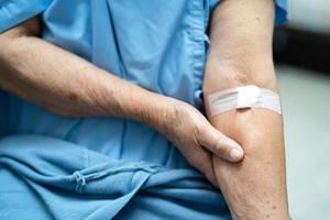 paciente asiático sênior ou idosa idosa mostra algodão para parar de sangrar, após teste de tiragem de sangue para verificação de saúde física anual para verificar o colesterol, a pressão arterial e o nível de açúcar. foto