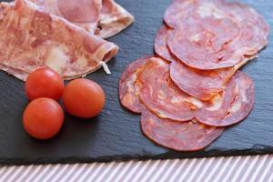 fatias frescas de salame e chouriço no quadro negro com três tomates cereja foto