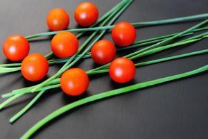 pequenos tomates-cereja vermelhos e cebola verde fresca em um fundo preto rústico, vista de cima, espaço de cópia foto