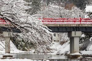 ponte nakabashi com queda de neve e rio miyakawa na temporada de inverno. marco de hida, gifu, takayama, japão. vista da paisagem foto