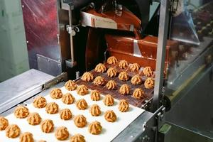 conceito de produção e indústria de doces - processamento de bombons de chocolate na esteira de confeitaria. foto