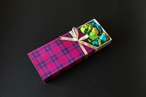 caixa de presente colorida com laço de cetim com estrelas de papel origami em fundo preto. presentes para os feriados. foto