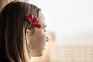 retrato de uma linda garota triste, olhando pela janela com esperança e expectativa. grampo de cabelo com corações. primeiro amor no dia dos namorados foto