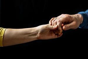 jovem casal de mãos dadas, mostrando amor e carinho, marido e mulher são ternamente unidos, mostrando apoio e compreensão foto