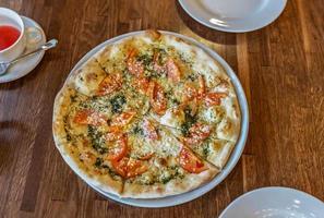 pizza quente fresca vegetariana em um prato branco. mesa servida em restaurante italiano foto