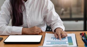 maquete em branco da tela do computador. A mão da mulher trabalha usando laptop com fundo branco para publicidade, informações de pesquisa de negócios na mesa do café. foto