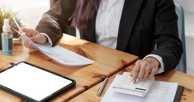 mulher com relatório financeiro e calculadora. mulher usando calculadora para calcular relatório na mesa do escritório foto