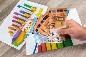 mão do homem segurando dinheiro de 50 euros e estatísticas foto