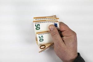 mão de homem contando notas de 50 euros foto