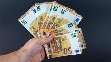 homem com notas de 50 euros foto