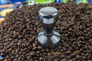 grãos de café com prensa de café de aço foto