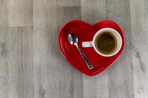 uma xícara de café com um pires em forma de coração foto