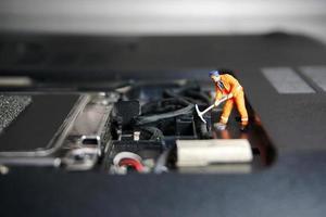 figura de trabalhador técnico de pé em uma unidade flash USB antiga. ele suporta o conceito. foto