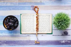 livro sagrado Alcorão e Rosário na mesa, close-up. foto
