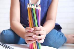 menina segurando muitos lápis de cor sentada no chão foto