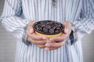 conceito de ramadã, mão segurando uma tigela de frutas de tâmara foto