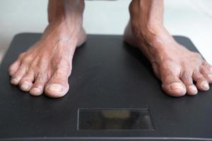 pés femininos seniores na balança de peso close up foto