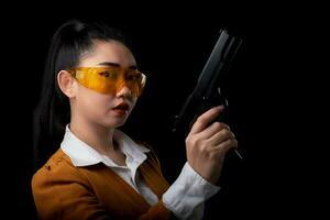 retrato linda mulher asiática vestindo um terno amarelo com uma das mãos segurando uma pistola para o fundo preto foto