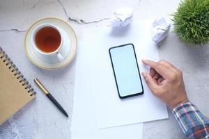 vista superior da mão do homem usando o telefone inteligente na mesa do escritório foto