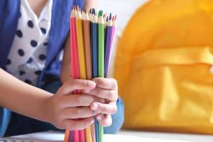 menina segurando muitos lápis de cor foto
