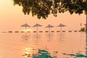 guarda-sol e cadeira ao redor da piscina com vista para o mar foto
