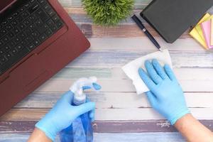 mão com luvas de borracha azul segurando frasco spray para limpar a mesa foto