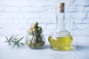 garrafa de azeite e azeitona fresca em um recipiente na mesa de madeira foto