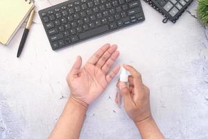 mão de jovem usando spray desinfetante para as mãos na mesa do escritório foto
