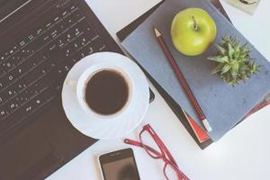 espaço de trabalho com laptop, xícara de café e livros, na mesa branca foto