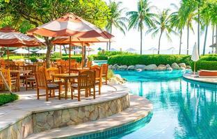 guarda-chuva com cadeira e mesa ao redor da piscina foto