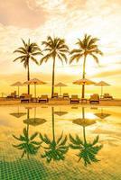 guarda-sol e cadeira ao redor da piscina em hotel resort para viagens de lazer e férias perto da praia do mar foto