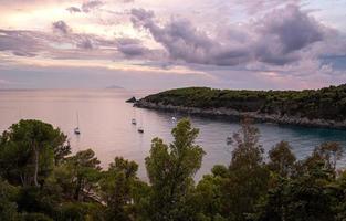 veleiros na água durante o pôr do sol dramático na baía de fetovaia, ilha de elba, toscana, itália foto