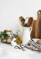 utensílios de cozinha, ferramentas e louças na parede de azulejos brancos de fundo. foto