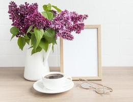 buquê de flores lilás em um vaso e moldura de madeira vazia foto