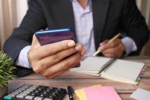 mão de jovem usando um telefone inteligente e escrevendo no bloco de notas na mesa do escritório foto
