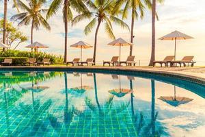 belo guarda-sol de luxo e cadeira ao redor da piscina ao ar livre em hotel e resort com coqueiro no céu do pôr do sol foto