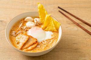Macarrão de arroz aletria com almôndega, porco assado e ovo na sopa picante foto
