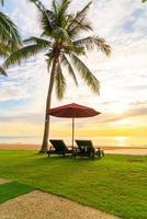 guarda-chuva com cadeira com fundo de praia de mar e nascer do sol pela manhã foto