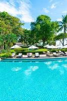 lindo guarda-sol e cadeira ao redor da piscina no hotel e resort foto