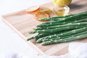 espargos verdes na tábua de cortar perto foto