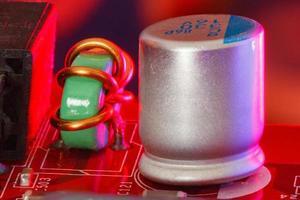 placa de circuito impresso eletrônico com componentes eletrônicos em vermelho foto