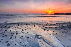 praia calma na hora do pôr do sol foto