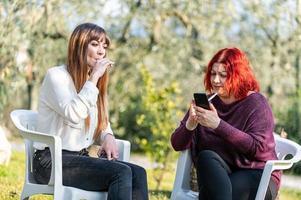 amigas usando smartphone e fumando cigarro foto