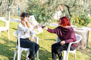 meninas brindam com uma taça de vinho tinto foto