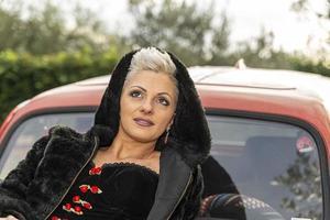 retrato de uma menina loira de cabelo curto deitada em cima de um carro foto