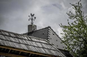 um cata-vento vintage em um telhado de madeira foto