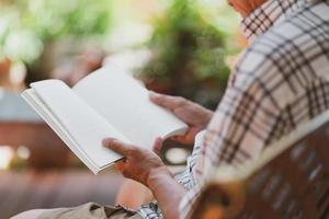 idoso asiático aposentado sentado no banco e lendo um livro no quintal de casa durante o tempo livre foto