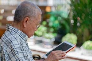 homem asiático sênior usando tablet para jogar mídia social em casa durante o tempo livre foto