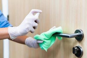 mulher desinfetando uma maçaneta de porta foto